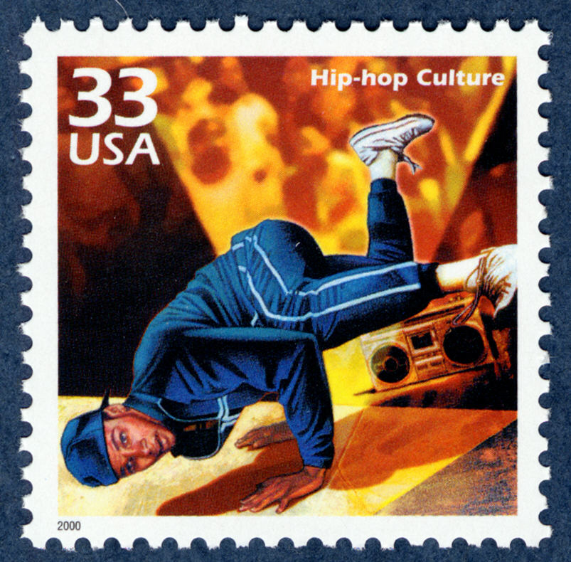 Postage stamp depicting breakdancing man standing on his hands with feet kicked in the air; boom box in background.