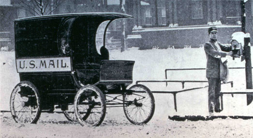 U.S. Mail motorized car in the snow and a postal worker next to a letter box