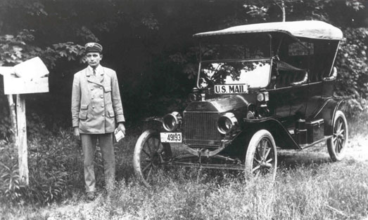 Rural letter carrier poses between a patron's mailbox and his new automobile