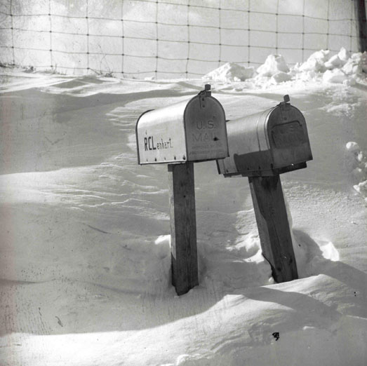 A pair of tunnel-shaped mailboxes stick out of a snowy drift along a road