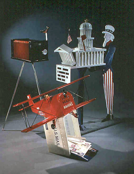 Uncle Sam, camera, and red plane-shaped folk art mailboxes on display