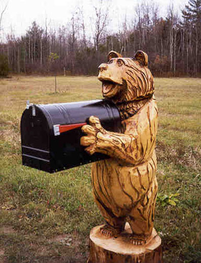 smiling bear carving holding a mailbox