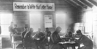 black and white photo of WWII soldiers sitting at tables next to a banner that says Remember to Write that Letter Home!