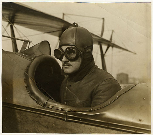 photo of Lipsner in a flight suit and goggles in the cockpit of a plane