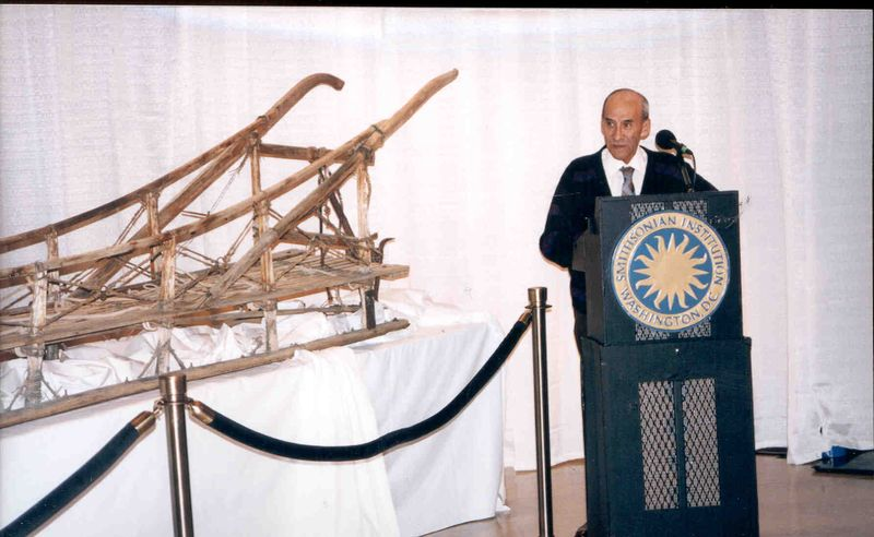 Charlie Biederman speaking at a podium next to the dog sled