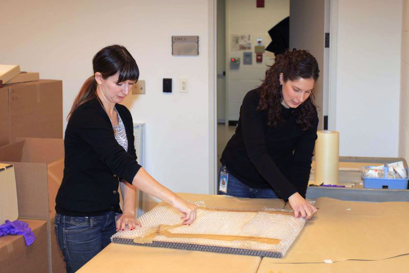 Annette Shumway with an intern unpacking a framed object