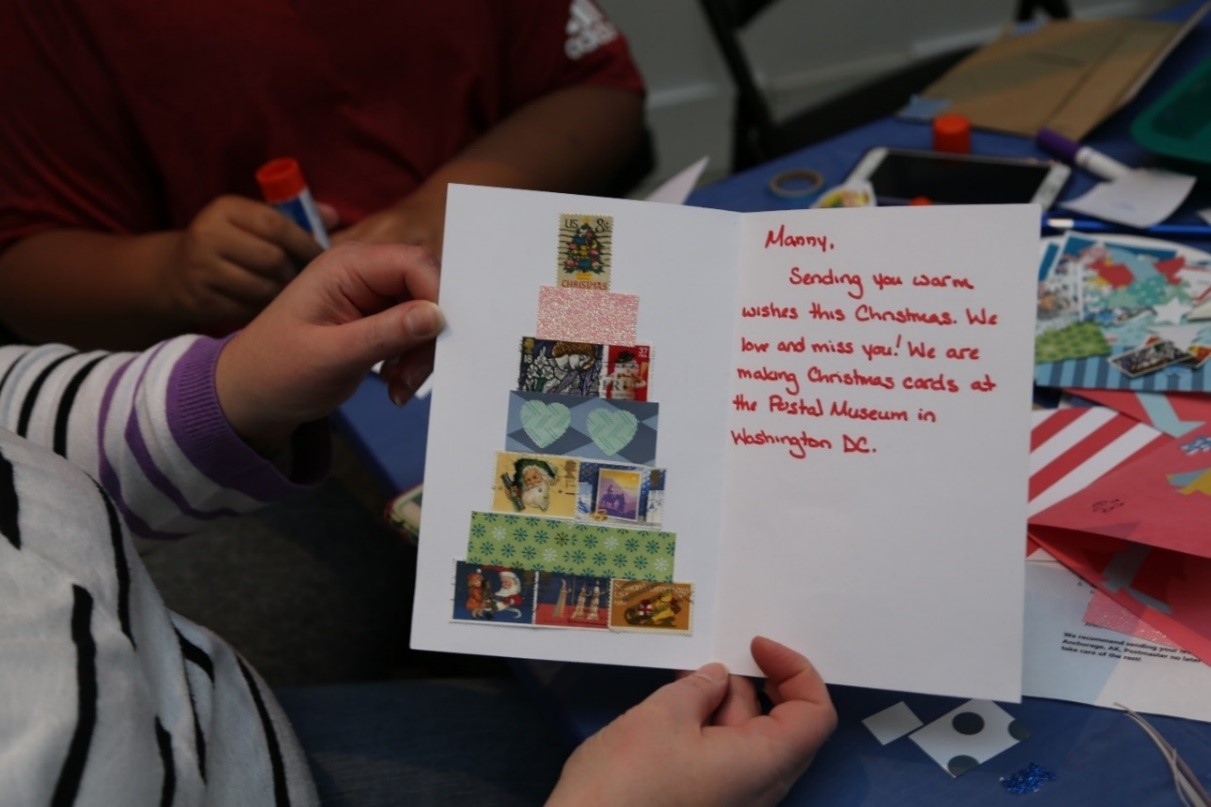 "Visitor holds up completed holiday card with the following message ""Manny, Sending you warm wished this Christmas. We love and miss you! We are making Christmas cards at the Postal Museum in Washington, DC."""