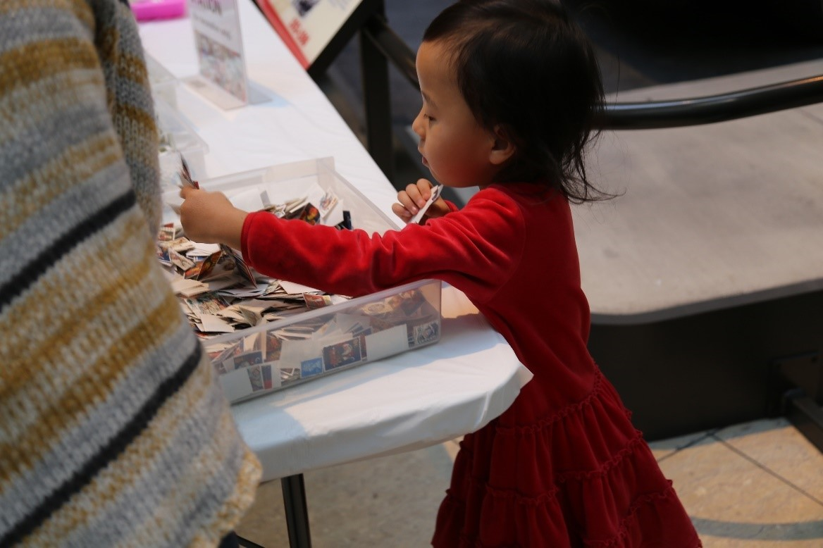 Young child selects postage stamps from a plastic bin