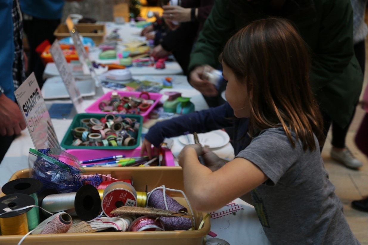 Visitors take ribbon, scissors, markers from table of craft supplies