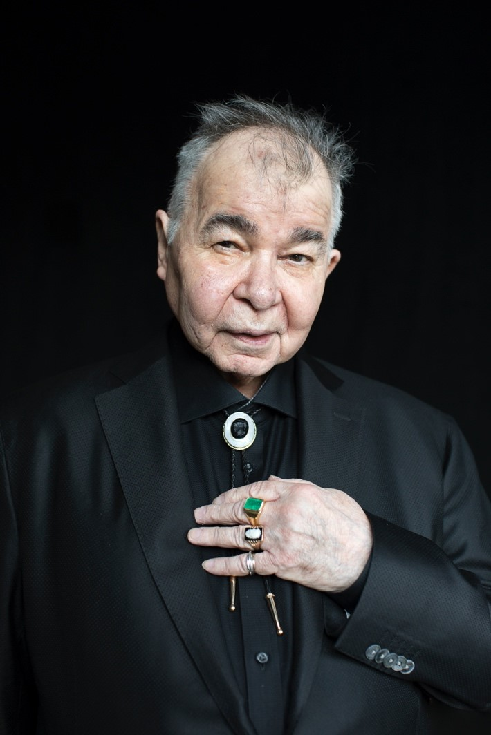 Photograph of John Prine from the torso up, looking into camera. He wears a black suit and shirt, white bolo tie, and several rings.