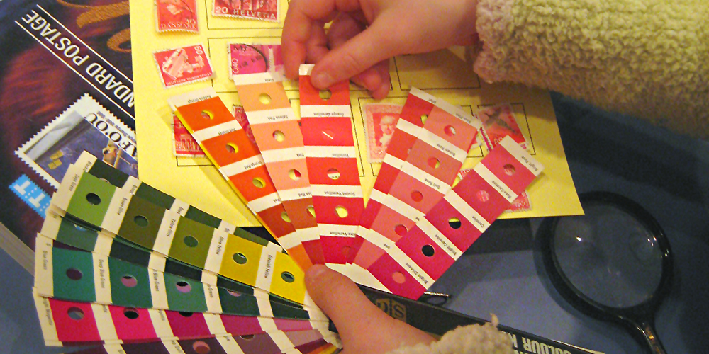 A child's hands hold color-scheme bookmarks above a yellow piece of paper with red stamps on it.