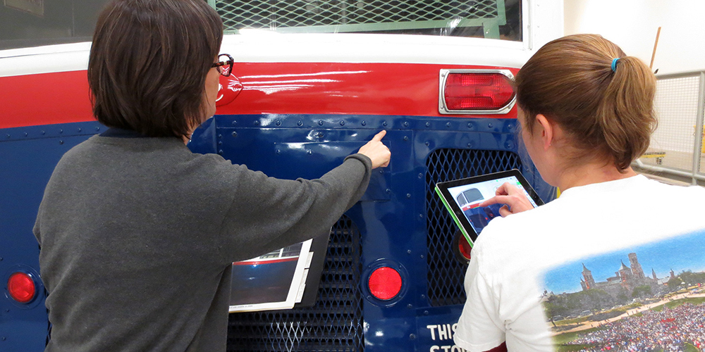 Two museum staff inspect the bus and make notes in the condition report