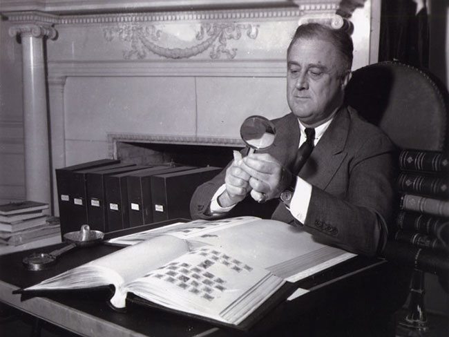 Franklin D. Roosevelt looking at a stamp through a magnifying glass