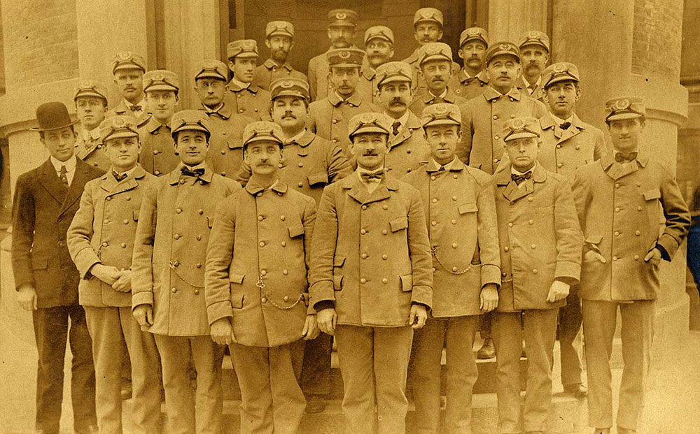 Twenty-four letter carriers, posing for the camera, circa 1900