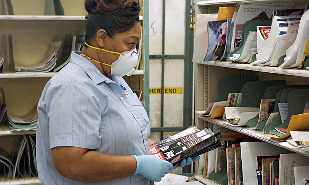 Postal worker wearing rubber gloves while sorting mail