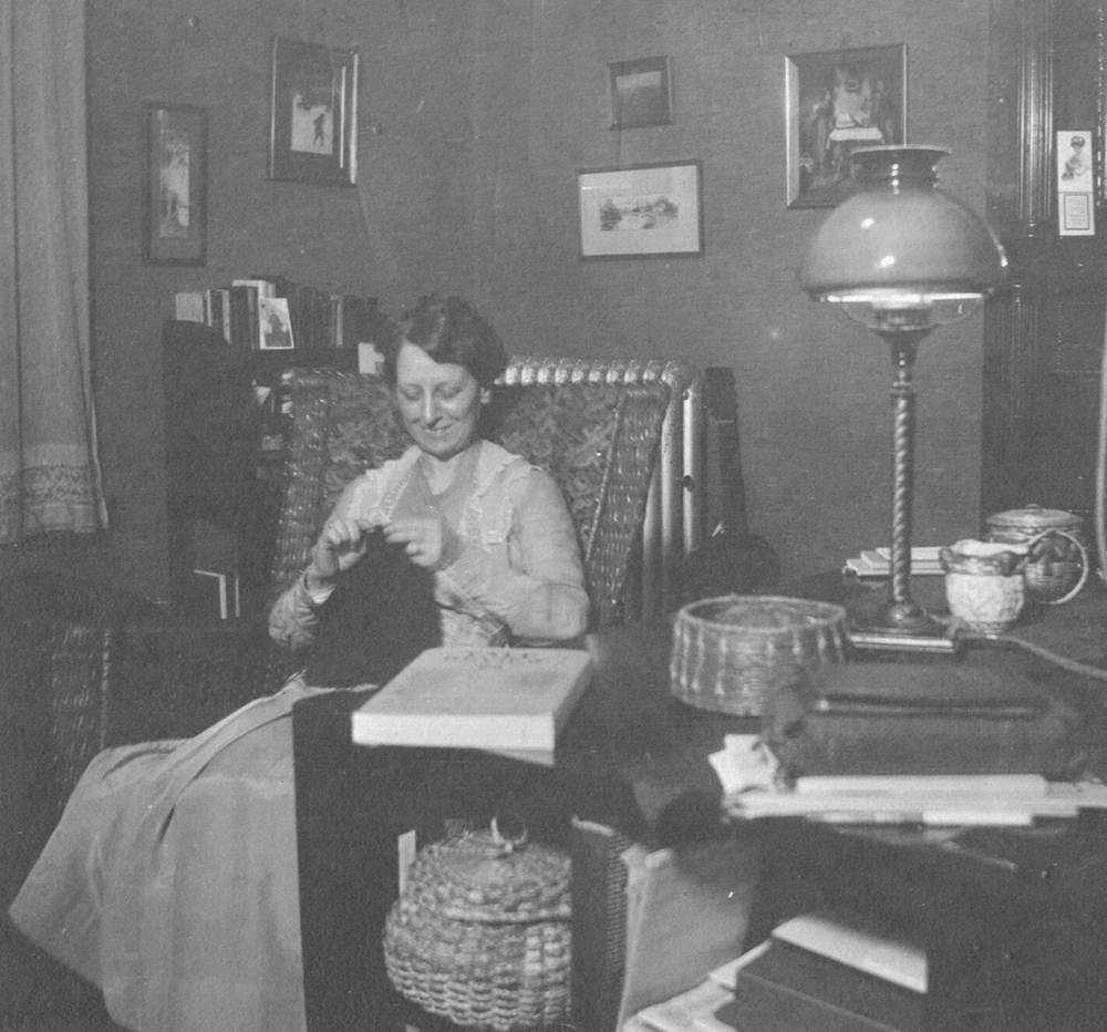 a smiling woman sitting in a chair, knitting a sweater