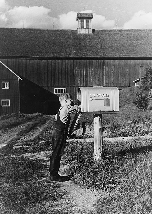 A young boy in overalls reaches into a mailbox bearing the name F.C. McNally.