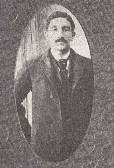 A black and white portrait of a young man. He is standing, and he wears an overcoat. He has a mustache, short hair, and a neutral expression. His gazes faces the camera.