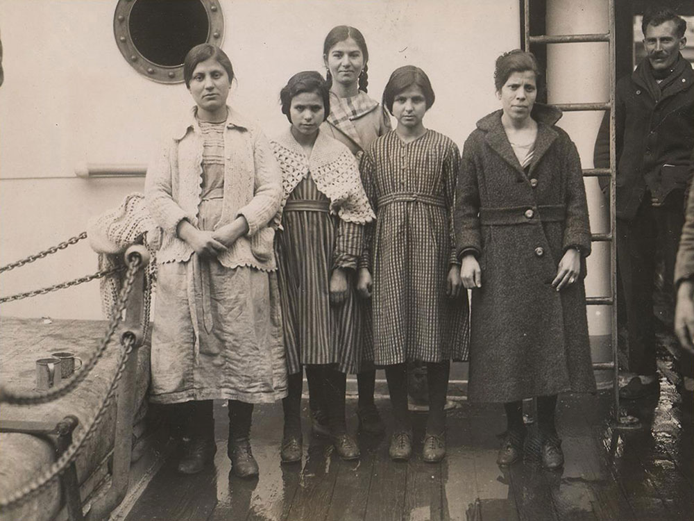 Five young women stand on the deck of a ship. Most wear neutral expressions, but one offers a small smile.