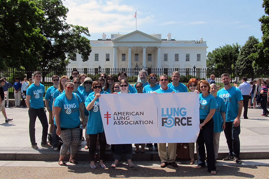 LUNG FORCE standing in front of the White House with Lung Force sign.