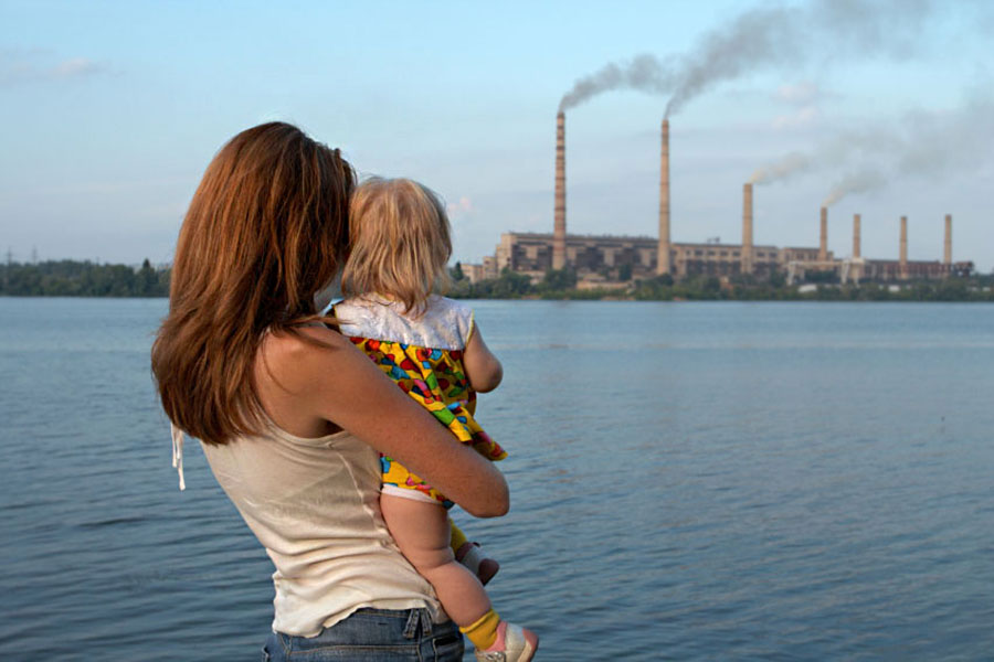 Woman with a baby looking at a power plant