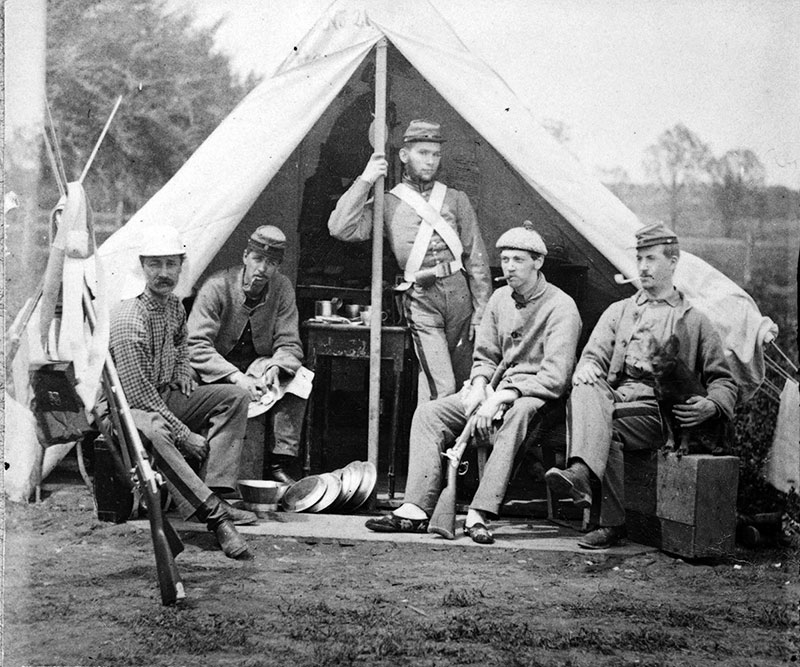 Civil War soldiers sitting and standing in front of a tent