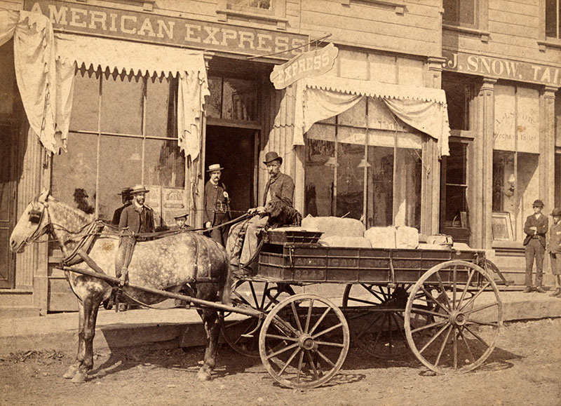 Horse and wagon with driver in front of an American Express office