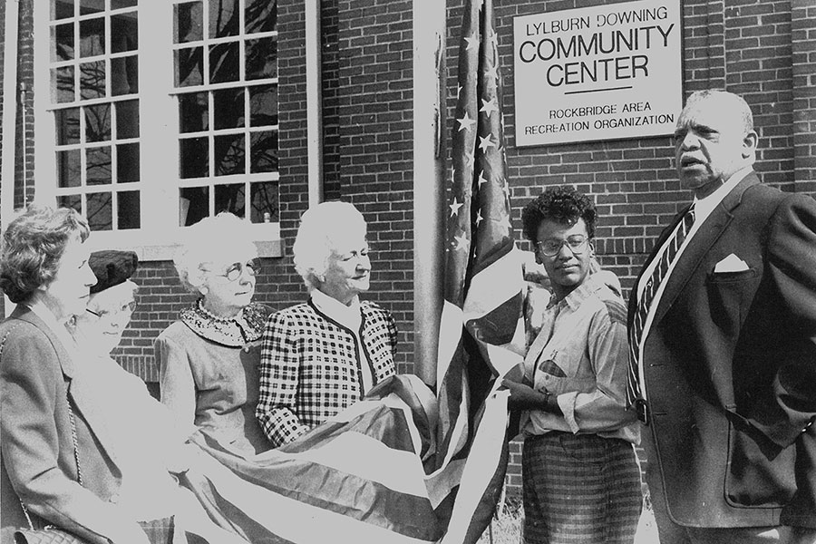 Six people dedicating a flag in front of a community center