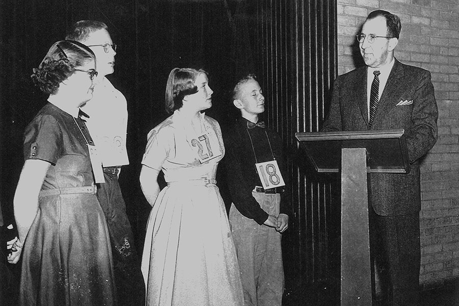 Four spelling bee contestants and a speaker behind a podium
