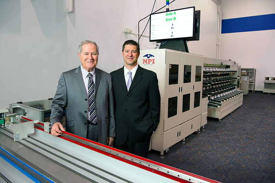 Henry and Brent Daboub standing in next to printing machinery