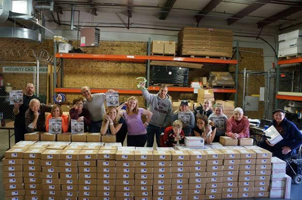 Employees posing behind stacks of boxes in a warehouse.