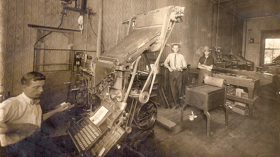 Newspaper employees working with a linotype and a proof press, circa 1916.