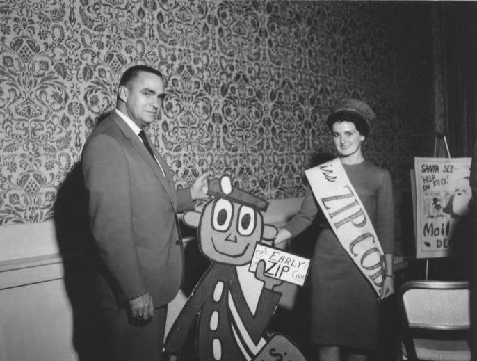 Doe Stella, from the Tucson, Arizona area, poses with Mr. Zip and the Post Office Department's Director of Customer Relations in 1964.