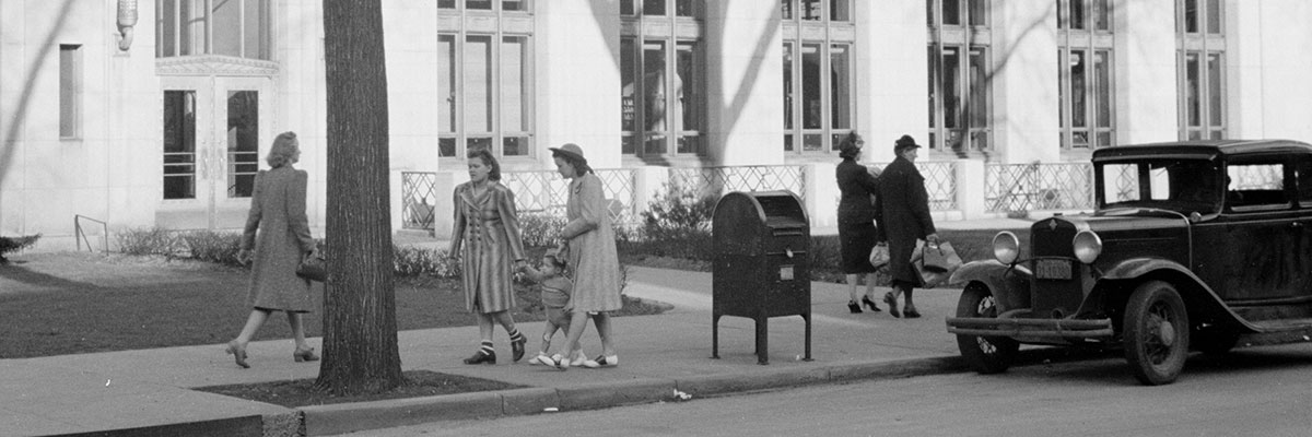 Five women and a child walking in front of the Main Post Office in Dubuque, Iowa, 1940