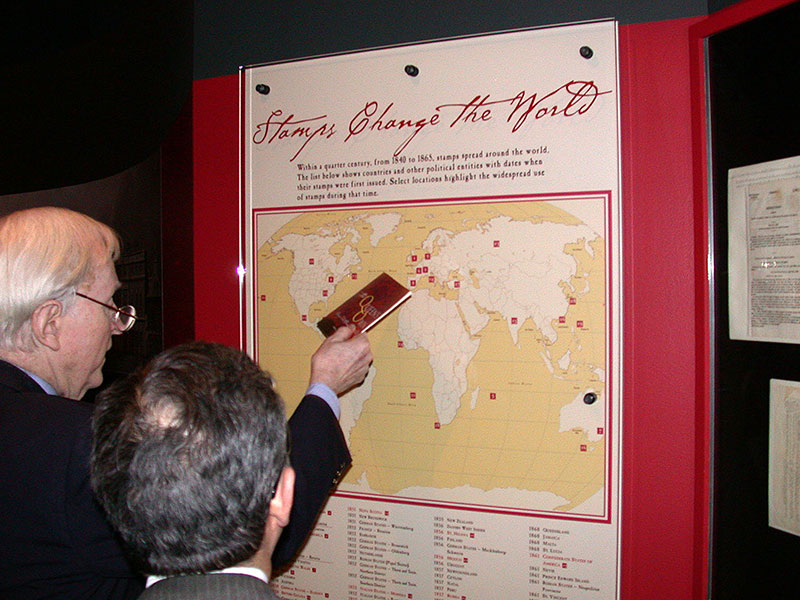 Two visitors looking at a map on the wall in the exhibition