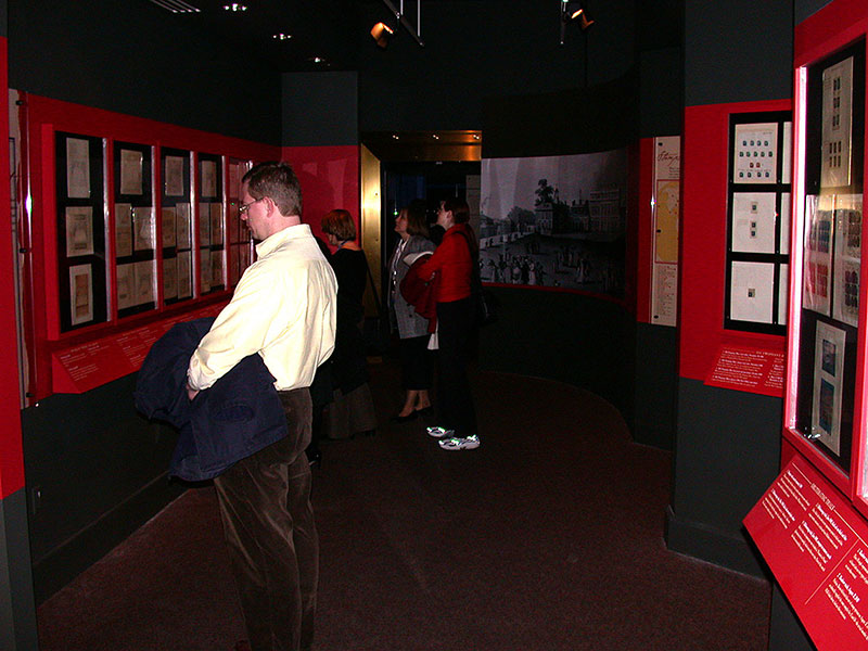 Four visitors reading panels in the exhibition