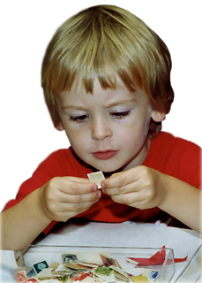 A boy looking closely at a postage stamp