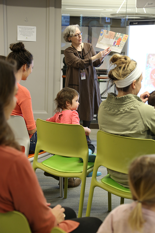 An adult standing and reading a children's book to an audience.