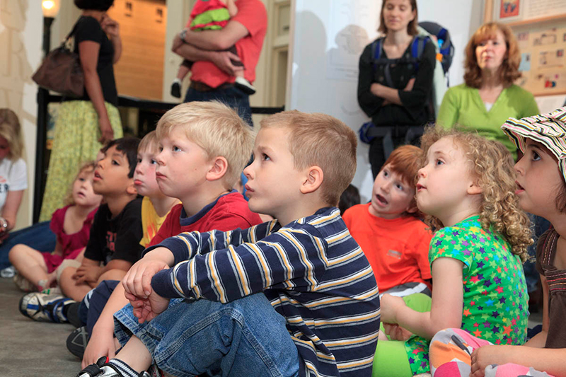 Young museum visitors listening to an educator read a story