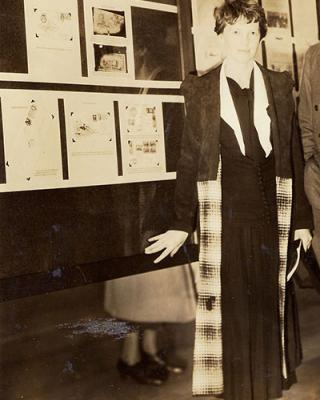 Amelia Earhart standing beside pictures of stamps