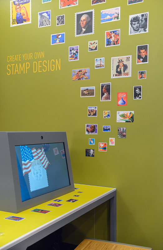 Stamp Design Station with a touch-screen monitor and pictures attached to the wall.